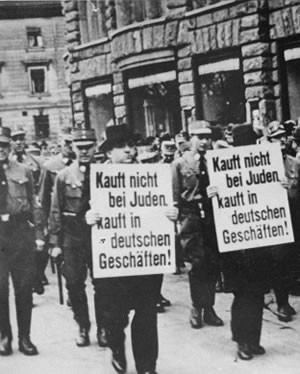 The Holocaust - Jewish businessmen are forced to march down a crowded Leipzig street while carrying signs